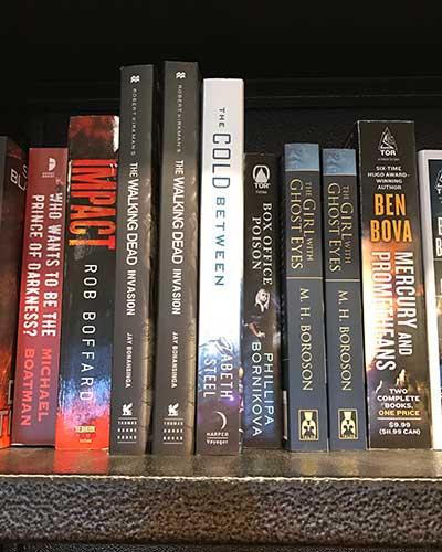 THE COLD BETWEEN spine on a bookstore shelf