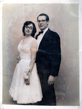 Woman in a wedding dress standing next to a man in a tuxedo